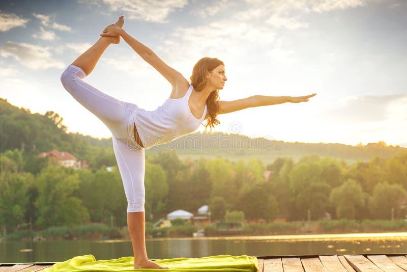 Woman doing yoga on the lake - beautiful lights stock photos