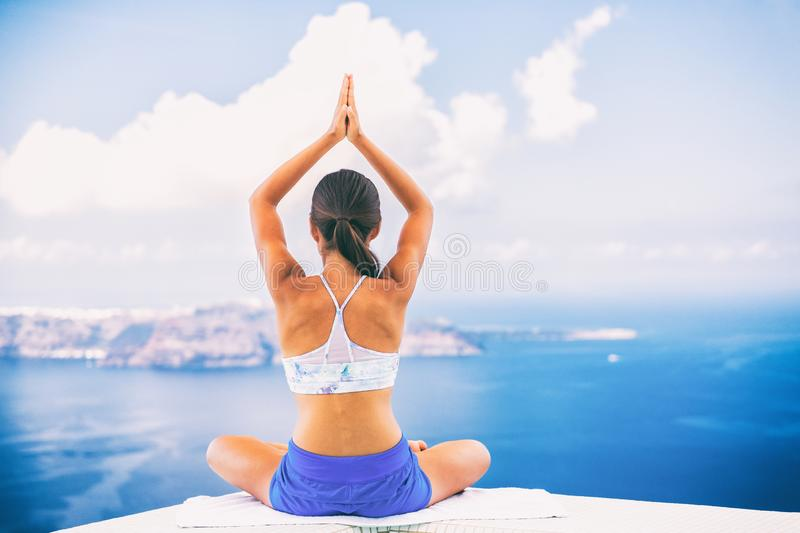 Woman doing yoga meditation in morning sunshine nature landscape- relaxing. In beach background royalty free stock image