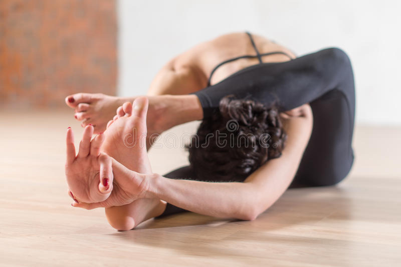 Woman doing yoga meditation and stretching exercise bending forward with her leg behind head stock images