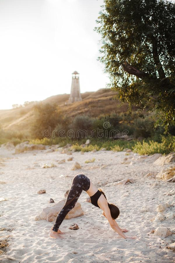 Young Woman Practicing yoga in the nature at sunset on sand beach against of lighthouse. Downward Facing Dog Pose Adho Mukha royalty free stock image