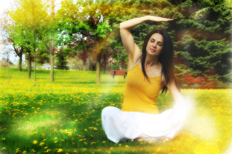 Woman doing yoga outdoors. Wellness woman doing yoga, reiki and meditation in the park. It's a beautiful sunny day, positive energy is all around stock photography