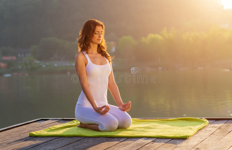 Woman doing yoga on the shore - half figure sitting royalty free stock images