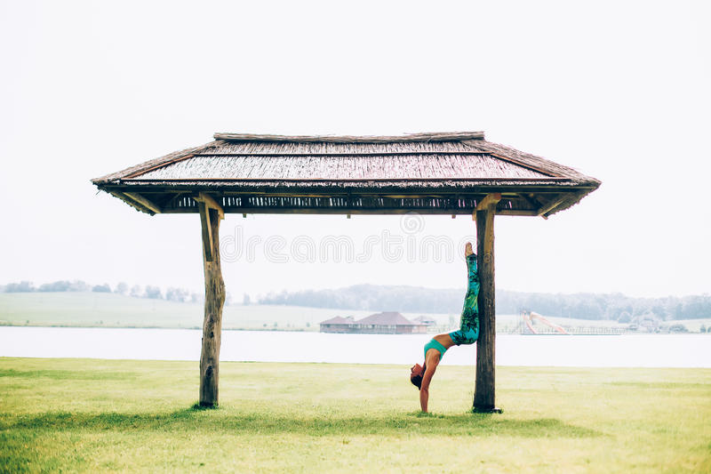 Woman doing yoga. Young woman doing yoga outdoors stock photo