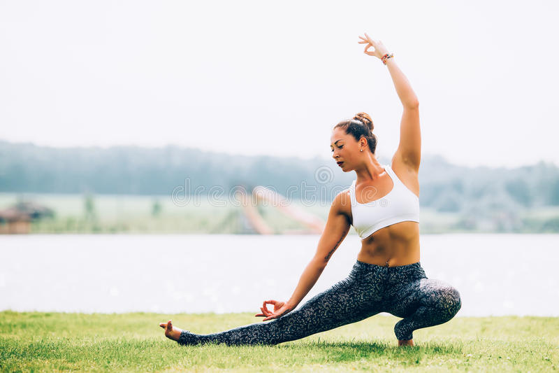 Woman doing yoga. Young woman doing yoga outdoors stock photography