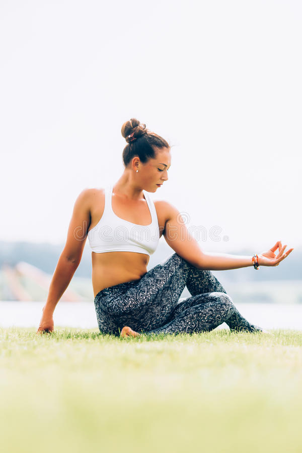 Woman doing yoga. Young woman doing yoga outdoors stock images
