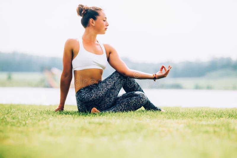 Woman doing yoga. Young woman doing yoga outdoors stock image