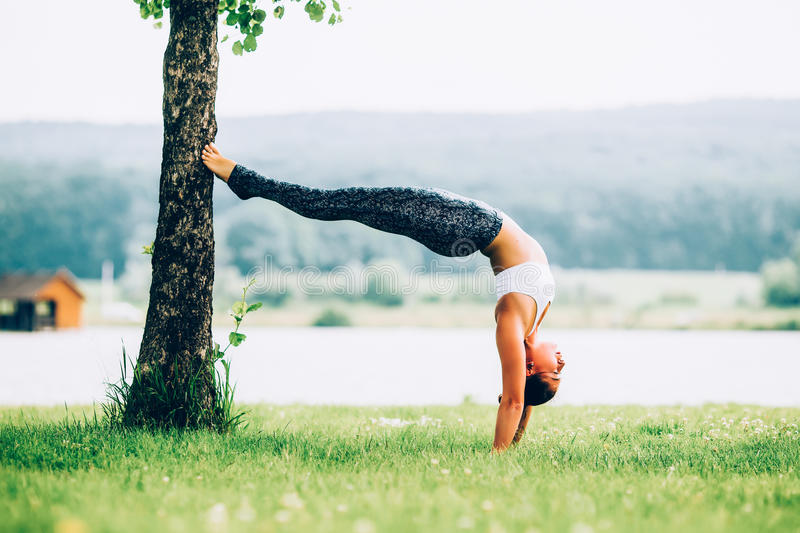 Woman doing yoga. Young woman doing yoga outdoors royalty free stock images