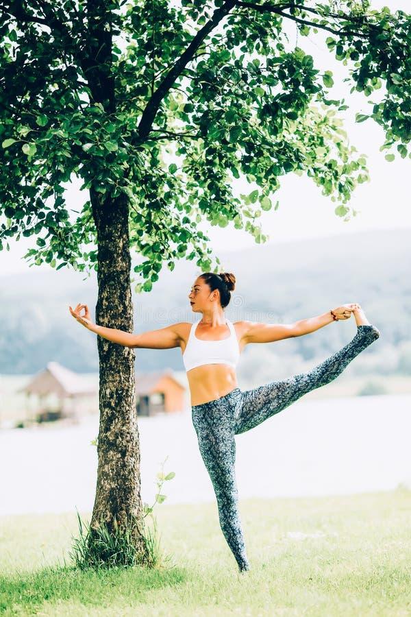 Woman doing yoga. Young woman doing yoga outdoors royalty free stock photo