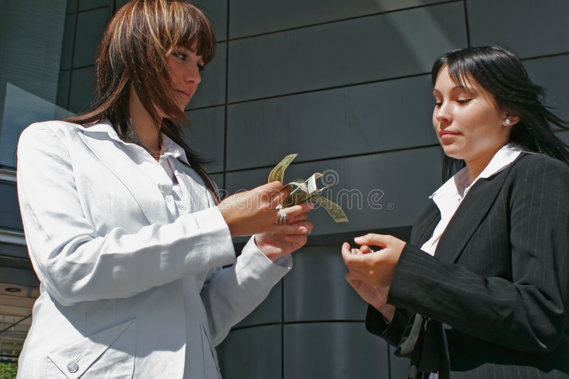 Woman and dollars. Women exchanging tickets of dollars in the street royalty free stock photography