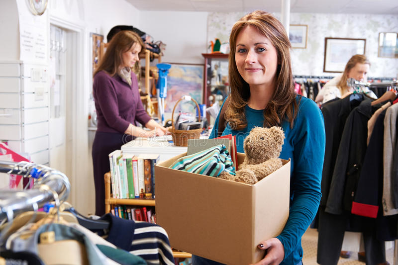Woman Donating Unwanted Items To Charity Shop stock photo