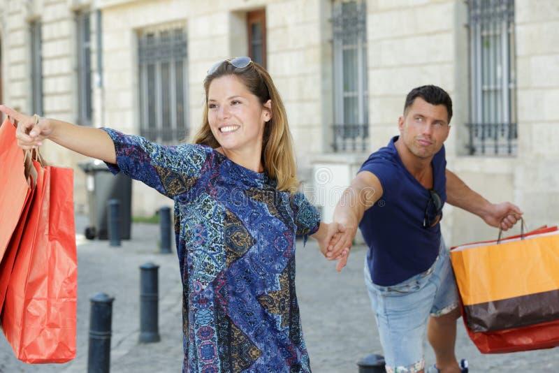 Woman dragging boyfriend to shop royalty free stock photos