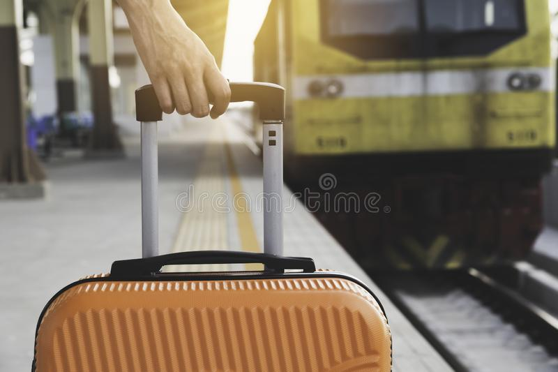 Woman dragging orange suitcase luggage bag, walking in train station. Travel concept royalty free stock photography