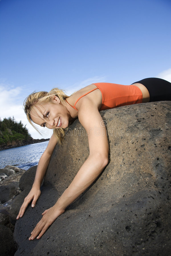 Woman draped over large rock. stock photo