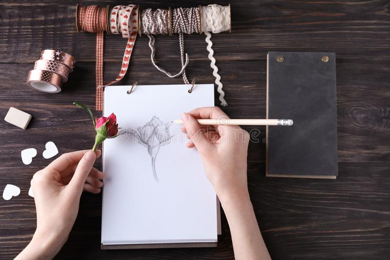 Woman drawing beautiful rose on sketch pad stock photography