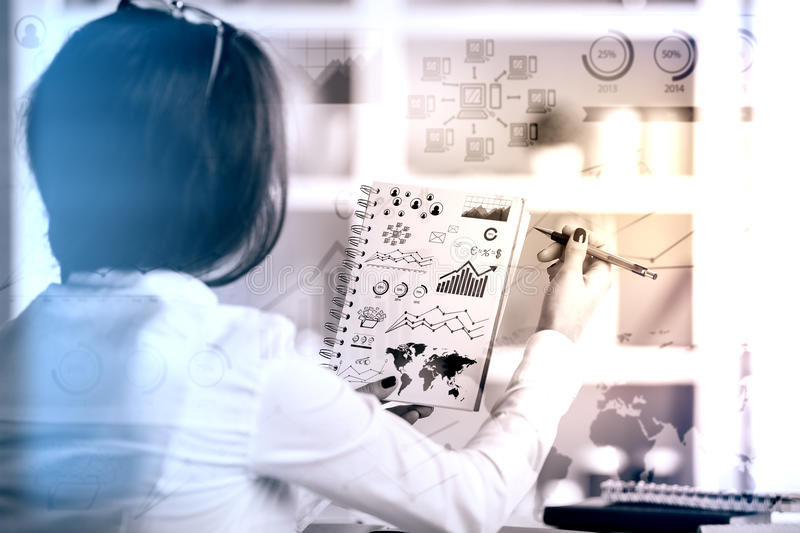 Woman drawing business graphs. Back view of young female drawing business graphs in spiral notepad. Filtered image royalty free stock photo