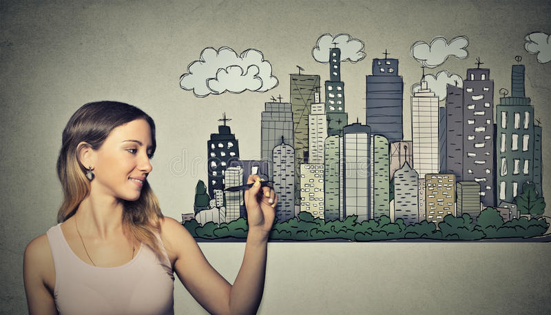 Woman drawing city skyline. Real estate development. Woman drawing city skyline on grey wall background. Real estate development, house market economy royalty free stock photography