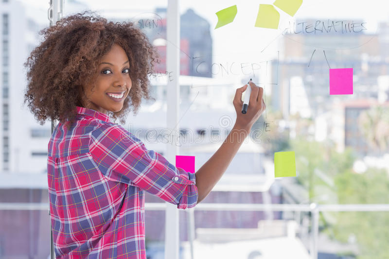 Woman drawing on flowchart and smiling at camera royalty free stock photos