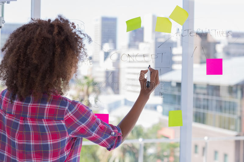 Woman drawing on flowchart with sticky notes. In bright office royalty free stock photography