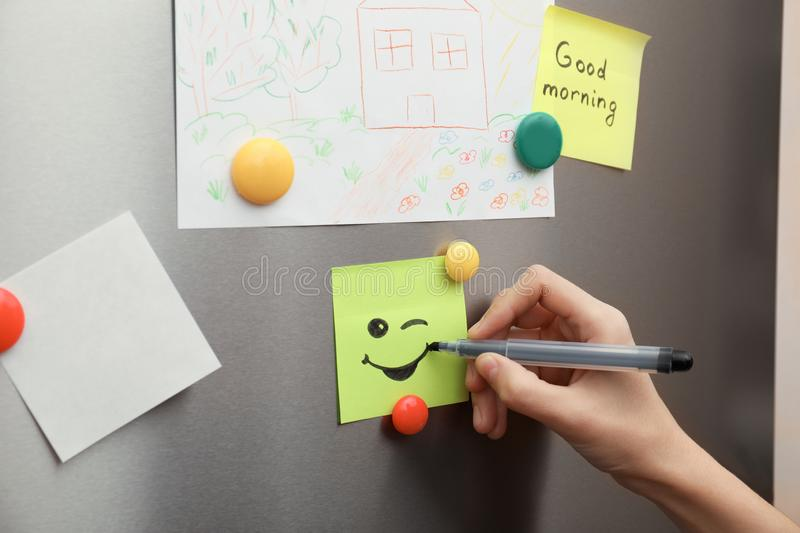 Woman drawing happy smile on note stuck royalty free stock images