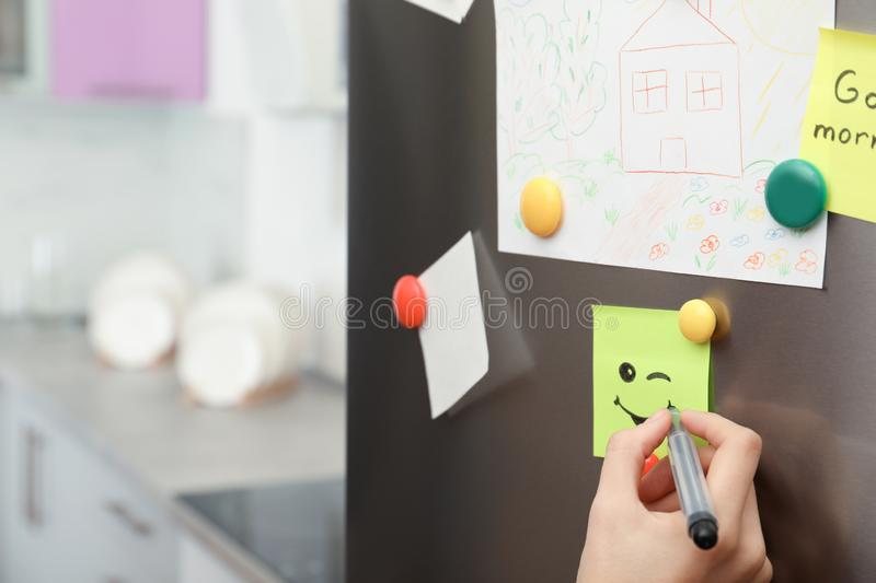 Woman drawing happy smile on note stuck royalty free stock photography