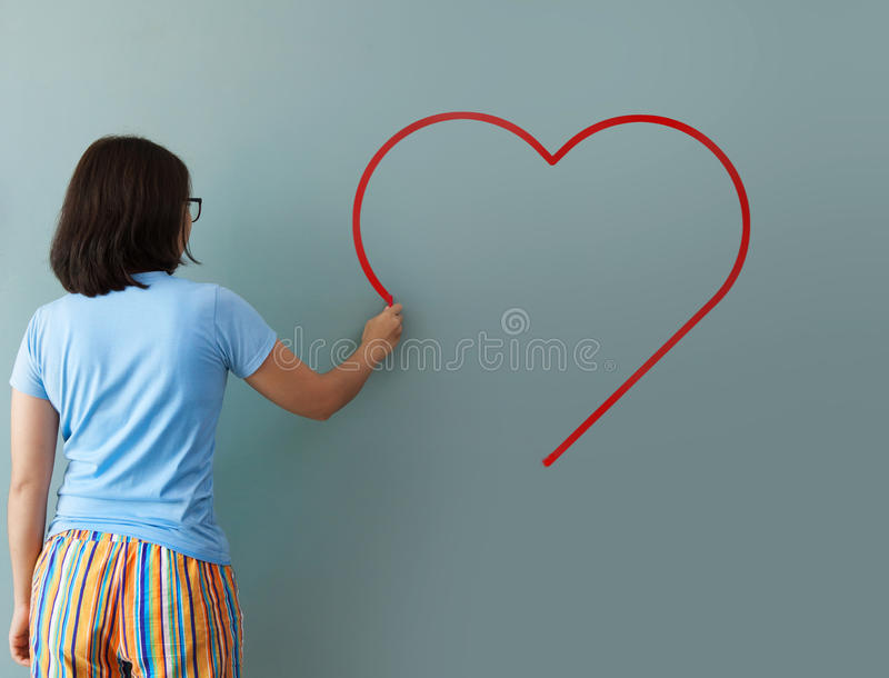 Woman drawing heart shape for valentines day with red chalk on w royalty free stock images