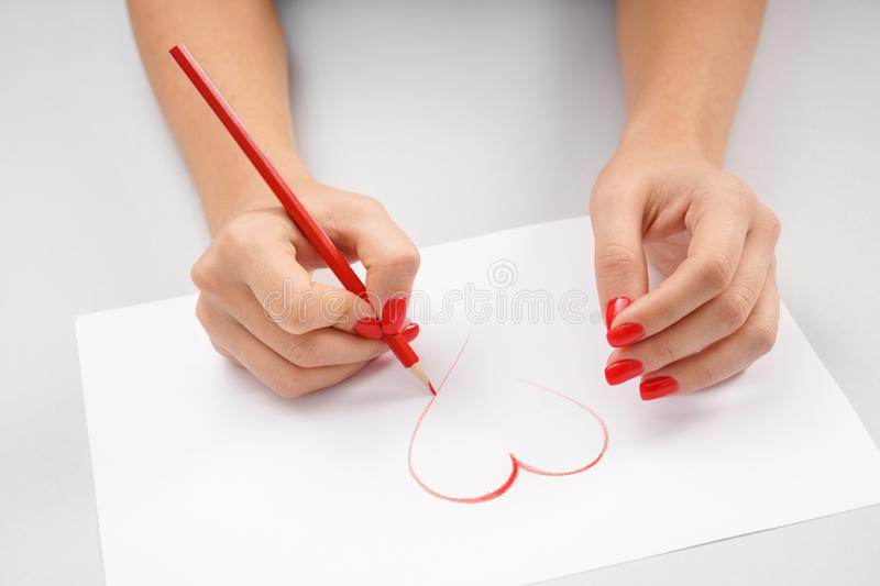 Woman drawing heart on sheet of paper royalty free stock images