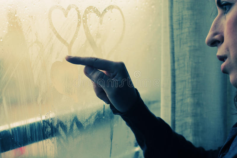 Woman drawing heart. On wet window royalty free stock images