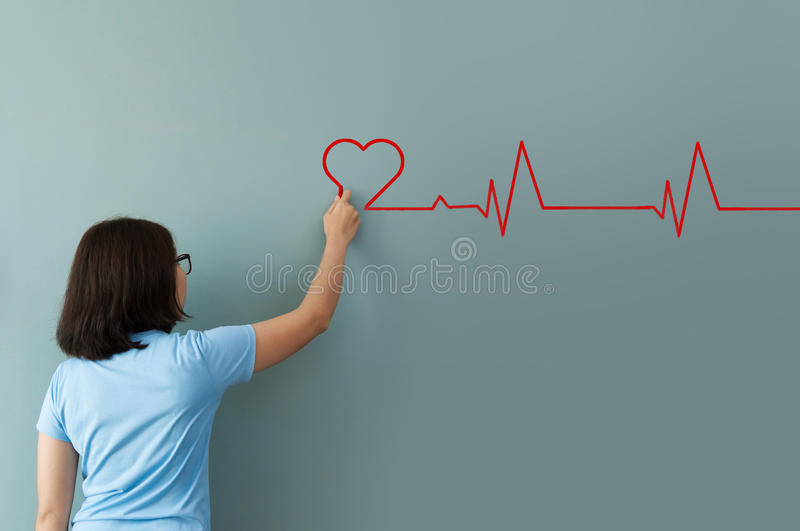 Woman drawing heartbeat with red chalk on wall. stock photography