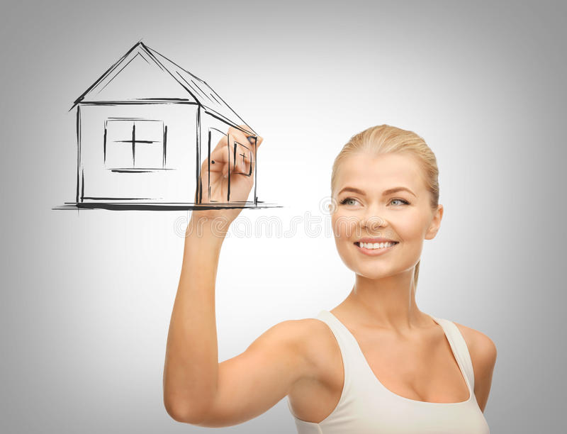 Woman drawing house on virtual screen. Real estate, technology and accomodation concept - woman drawing house on virtual screen royalty free stock photo