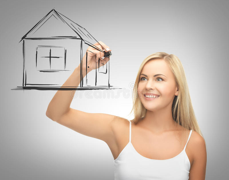 Woman drawing house on virtual screen. Real estate, technology and accomodation concept - woman drawing house on virtual screen stock photo