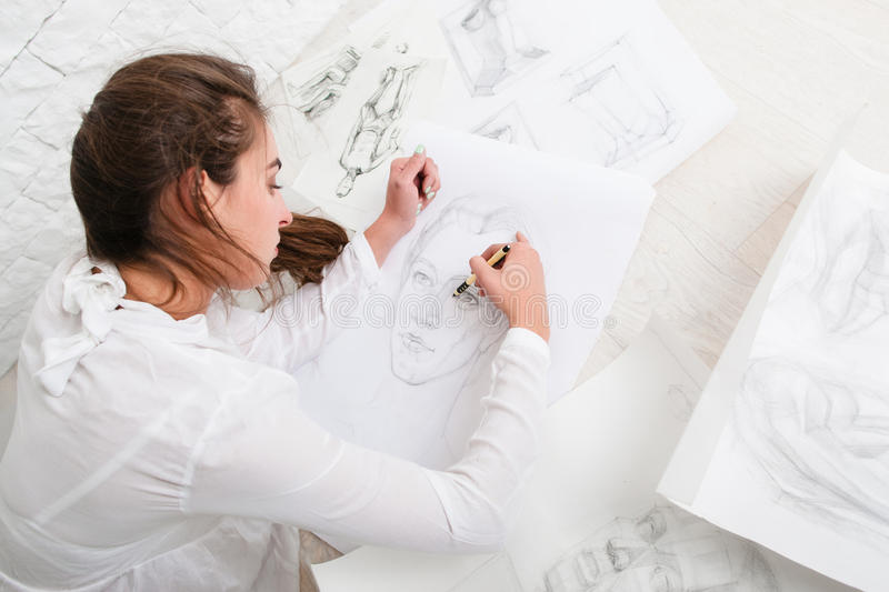 Woman drawing pencil portrait on floor in workshop royalty free stock photos