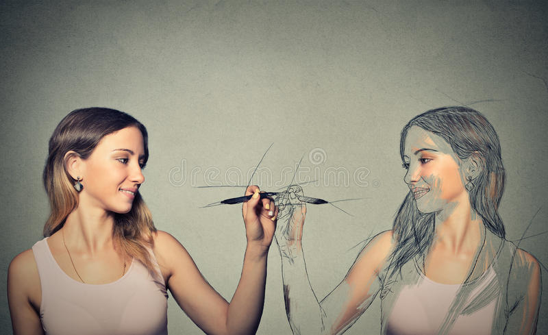 Woman drawing a picture, sketch of herself royalty free stock photography