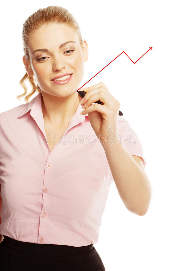Woman drawing on a virtual screen. Attractive young woman drawing on a virtual or glass screen using a red felt tip pen to draw a graph during a presentation stock photos
