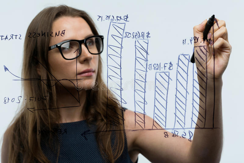 Woman draws various growth charts, calculating prospects for success in a modern glass office royalty free stock photo