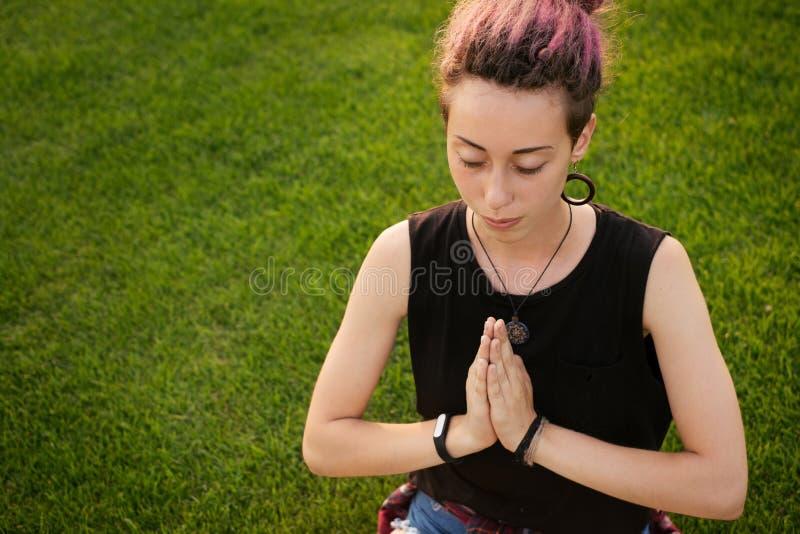 Woman with dreadlocks doing yoga exercises outdoors stock photos