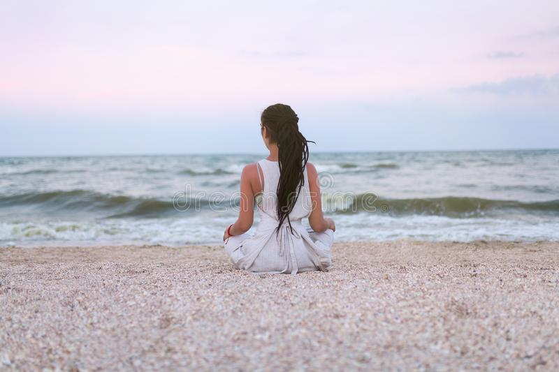 Woman practices yoga and meditates in the lotus position on the beach stock photo