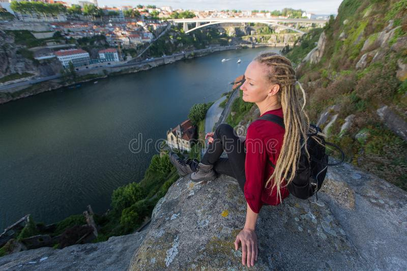Woman with dreadlocks sitting on a rock and looks at Douro river, Porto. royalty free stock images