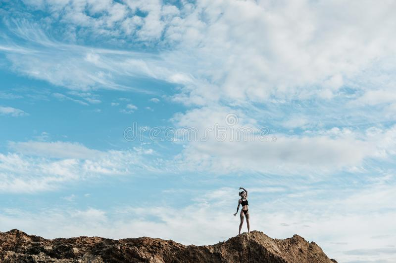 A woman with dreadlocks in underwear and tattooed stands on a sandy hill in the distance. Blue sky with clouds, copy. Space. The concept of freedom and unity royalty free stock images