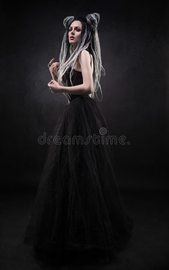 Woman with dreads and black gothic dress. Posing on dark background royalty free stock image