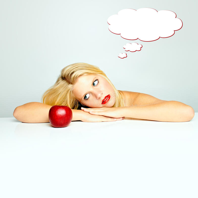 Woman dreaming. Woman looking at apple dreaming royalty free stock image