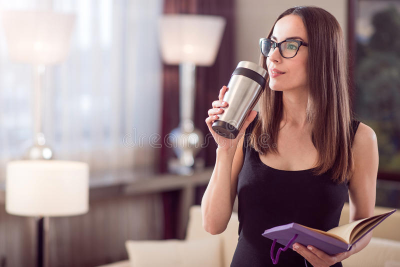 Woman dreaming and holding thermo mug. Coffee time. Charming beautiful young woman standing and dreaming while holding a thermo mug and an open notebook stock photography