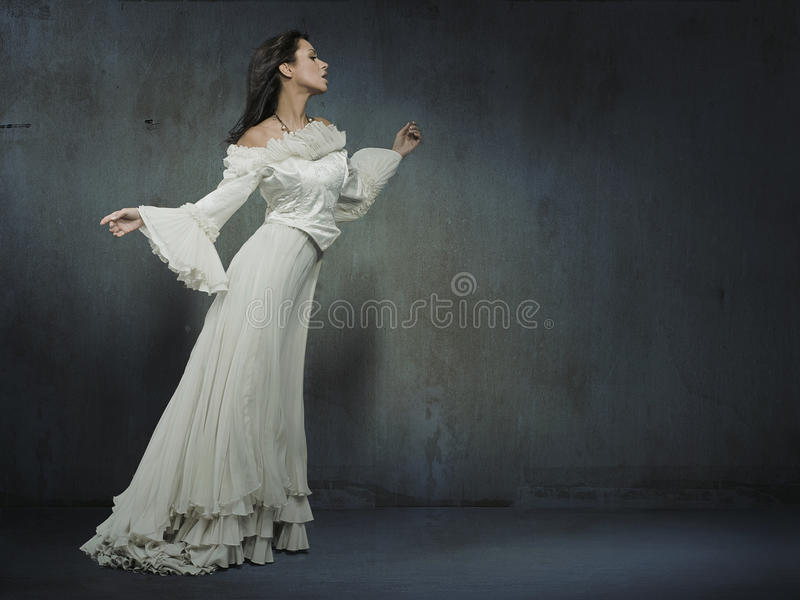 Woman in dress. Beautiful woman wearing white dress over a grungy wall