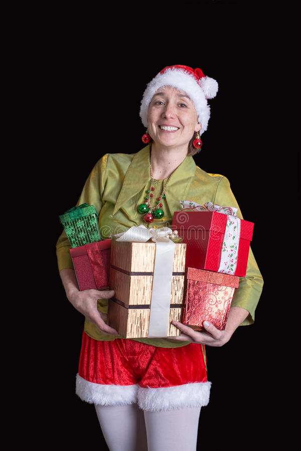 Woman dress in Christmas elf costume with gifts stock image