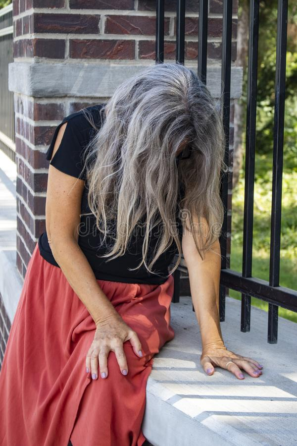 Woman in dress sits by fence with her head bowed and face covered with long gray hair sick or sad or in distress. A Woman in dress sits by fence with her head royalty free stock photo