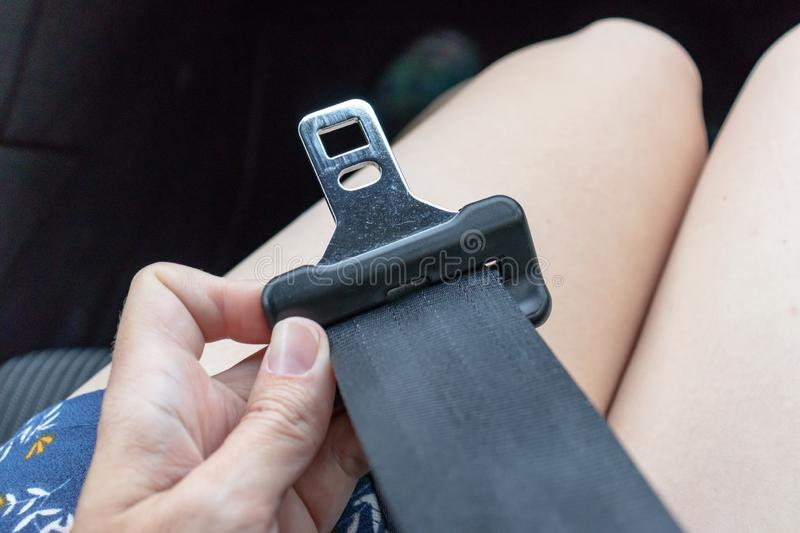 Woman in a dress sitting in car and holding a buckle of a seatbelt, safety belt in hand close up, automobile driver protection and stock image