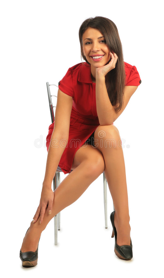 Woman in dress sitting on chair stock photo