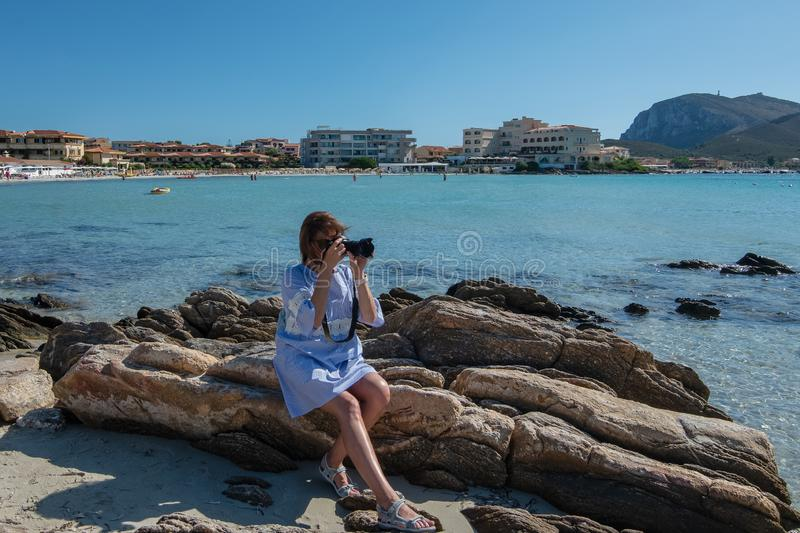Woman in a dress sitting on the rocks on the beach and taking pictures with a SLR camera. Sea and mountains in the background stock image