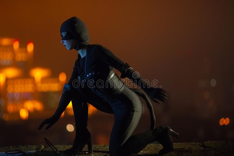 A woman dressed as a cat in a black costume, gloves and a mask, sits against the background of night lights and sky. A woman dressed as a cat in a black cose royalty free stock images