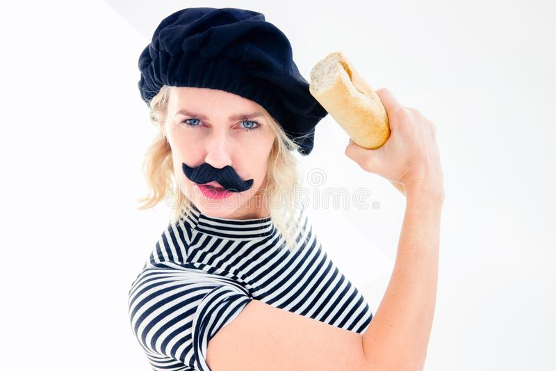 Woman dressed as french man with mustache and beret holding bag stock photo