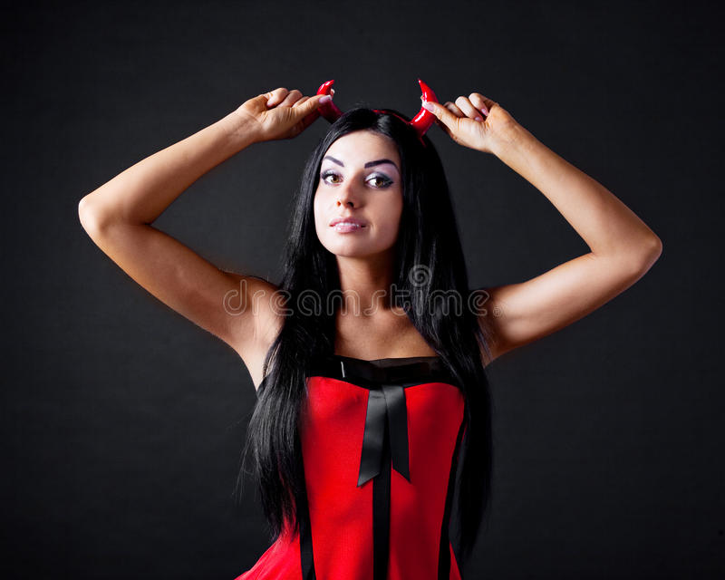 Woman dressed as an imp. Brunette girl wearing a halloween costume of an imp, against black background stock images